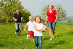Happy family running through a park